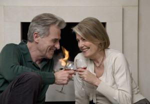 Senior couple sipping win by fireplace